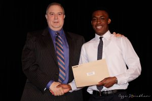 Lamond Dennis (right) accepts the award from Coach Andrew Hertzog